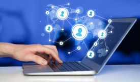 Close up of hand with laptop and social media icons. Close up of hand with laptop and social media network icons Royalty Free Stock Image