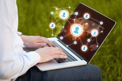Close up of hand with laptop and social media icons Royalty Free Stock Images