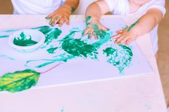 Close up of hand little children drawing with green paint on autumn leaves. royalty free stock images