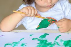 Adorable child painting fall leaves at table. stock images