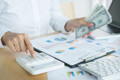 Close up hand of man counting money with calculator and making n Royalty Free Stock Image
