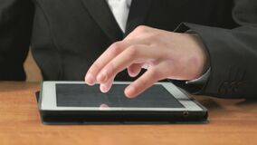 Man looking at photos using computer tablet. Close-up of hand of man dressed in black suit sits at desk at office the resting and looking at favorite photos stock video footage