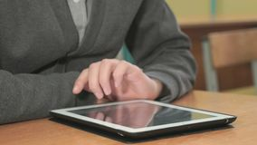 Man looking at photos using computer tablet. Close-up of hand of man dressed in grey sweater sits at desk at office the resting and looking at favorite photos stock video