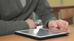 Man looking at photos using computer tablet. Close-up of hand of man dressed in grey sweater sits at desk at office the resting and looking at favorite photos stock footage