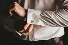 Close up of a hand man how wears unusual cufflink on a white shirt. Closeup of a hand man how wears unusual cufflink on a white shirt stock photography
