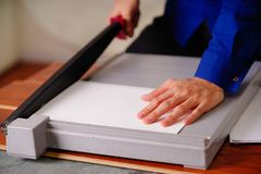 Close up of hand man over the guillotine, working on the guillotine, cutting paper.  Stock Photos