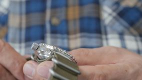 Close-up of the hand of a man in a plaid shirt who holds and views a diving watch on a nylon strap. Close-up of the hands of a man in a plaid shirt who holds stock footage