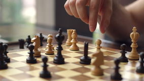 Close-up of the hand of a man playing chess.