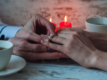 Close up on hand of a man put on an engagement ring on the finger of the bride. Close up. St. Valentine`s day Royalty Free Stock Photo