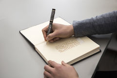 Close up of a hand of a man ready to write on a notebook. Man writing. Close up of a hand of man ready to write on a notebook with a nicely carved pen Stock Images