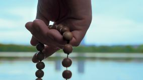 Close-up, Hand of Man with Rosary Reads Prayer on River Background. Close-up, Hand of Man with Rosary Reads Prayer on the River Bank in the Evening stock footage
