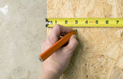Close up of hand marking plywood for construction project Stock Photo