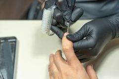 Close-up of the hand of the master and manicure machine royalty free stock images