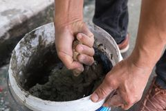 Close up hand mixing cement or concrete by trowel royalty free stock photo