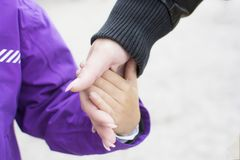 Close up hand of mother holding and lead her child in winter season, care concept Stock Photo