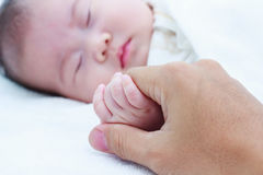 Close up hand of parent clasping hand of sleeping child. Stock Photos