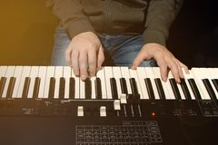 Close-up of hand person playing a piano keyboard in spotlights, front view royalty free stock images