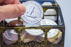 Litecoin Treasure Chest. Close up of a hand picking out a Litecoin coin from a treasure chest Royalty Free Stock Image