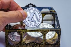 Litecoin Treasure Chest. Close up of a hand picking out a Litecoin coin from a treasure chest Stock Photography