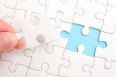 Close up of hand placing the last jigsaw puzzle piece royalty free stock image