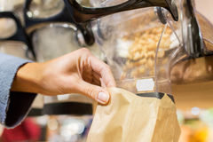 Close up of hand pouring nuts to paper bag Royalty Free Stock Photography