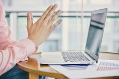 Close up hand praying for victims in front of a laptop.  Stock Image