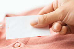 Close up of hand with price tag and clothing item Stock Photo
