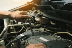 Close up of hand professional mechanic repairing a car in auto repair shop royalty free stock photos