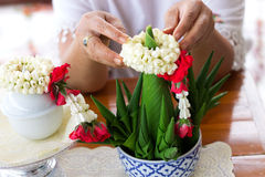 Close- up the hand put Jasmine garland on the top of Rice offeri Royalty Free Stock Photography