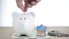 Close up of hand putting coin into piggy bank. Saving money for home building concept stock video footage