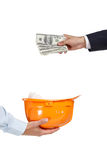 Close up of hand putting dollars in helmet Stock Images