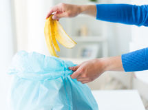 Close up of hand putting food waste to rubbish bag Royalty Free Stock Photo