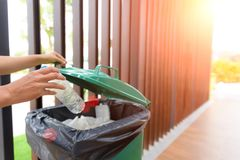 Close up Hand putting plastic bottle waste into garbage trash,. With selective focus Royalty Free Stock Photo