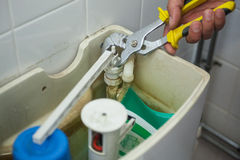 Close up of hand repairing toilet Royalty Free Stock Photo