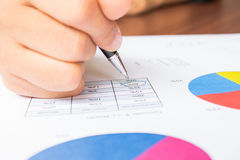 Close up of hand reviewing accounting documents. Close up of hand with Pen reviewing accounting documents Royalty Free Stock Photography