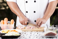 Close up of Hand's Chef cutting raw pork on wooden board Stock Photos