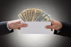 Close-up of hand's holding envelop full of currency note Stock Image