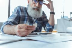 Serious senior male in glasses is working with concentration royalty free stock photo
