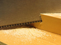 Close up of a hand saw cutting a piece of wood on a wooden work. Bench Royalty Free Stock Photos