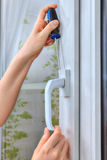Close-up of hand with screwdriver is dismantling plastic window. Close-up of the dismantling of an old window handle on a white pvc window Stock Photography