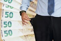 Man turns up his trouser pocket. Background of 50 euro in the background. stock image