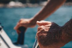 Close-up of Hand of Senior Captain on steering wheel of motor boat. stock photography