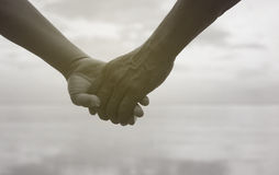 Close up hand of senior couple holding hand together near seaside at the beach,black and white picture color Royalty Free Stock Photography