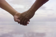 Close up hand of senior couple holding hand together near seaside at the beach,filtered image,light effect added,selective focus Royalty Free Stock Images