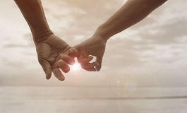 Close up hand of senior couple hook each other's little finger together near seaside at the beach Stock Photos