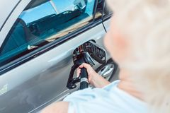 Close-up of the hand of a senior woman filling up the gas tank of her car. Side view close-up of the hand of a senior woman holding the pump, while filling up royalty free stock photo