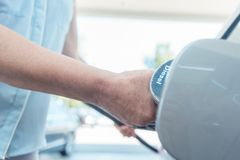 Close-up of the hand of a senior woman filling up the gas tank of her car. Side view close-up of the hand of a senior woman holding the pump, while filling up royalty free stock photography