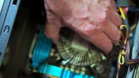 Close-up of hand serviceman uninstall CPU heatsink shows it .