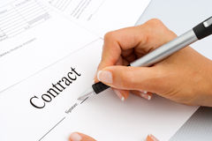 Close up of hand signing contract documents. Macro Close up of female hand signing contract documents stock photo