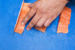 Close up of hand slicing raw salmon with sharp knife Stock Photography